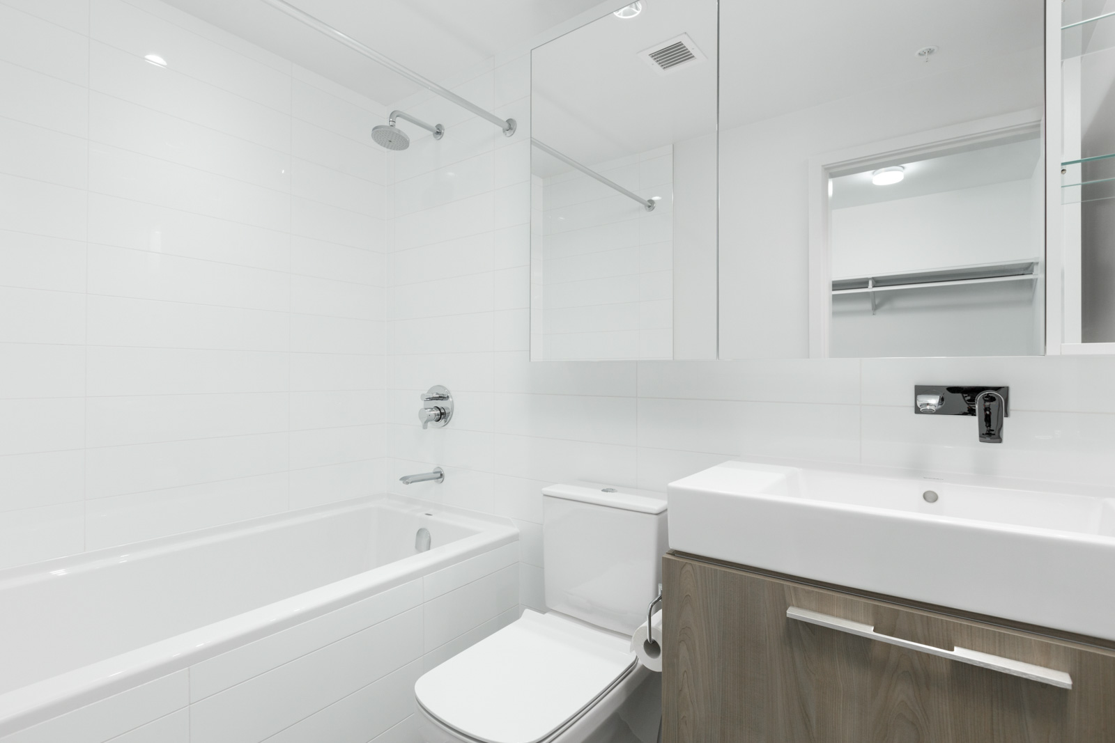 bathroom with toilet in middle and vanity on right and shower and tub on left in brand new condo at brentwood tower one in burnaby