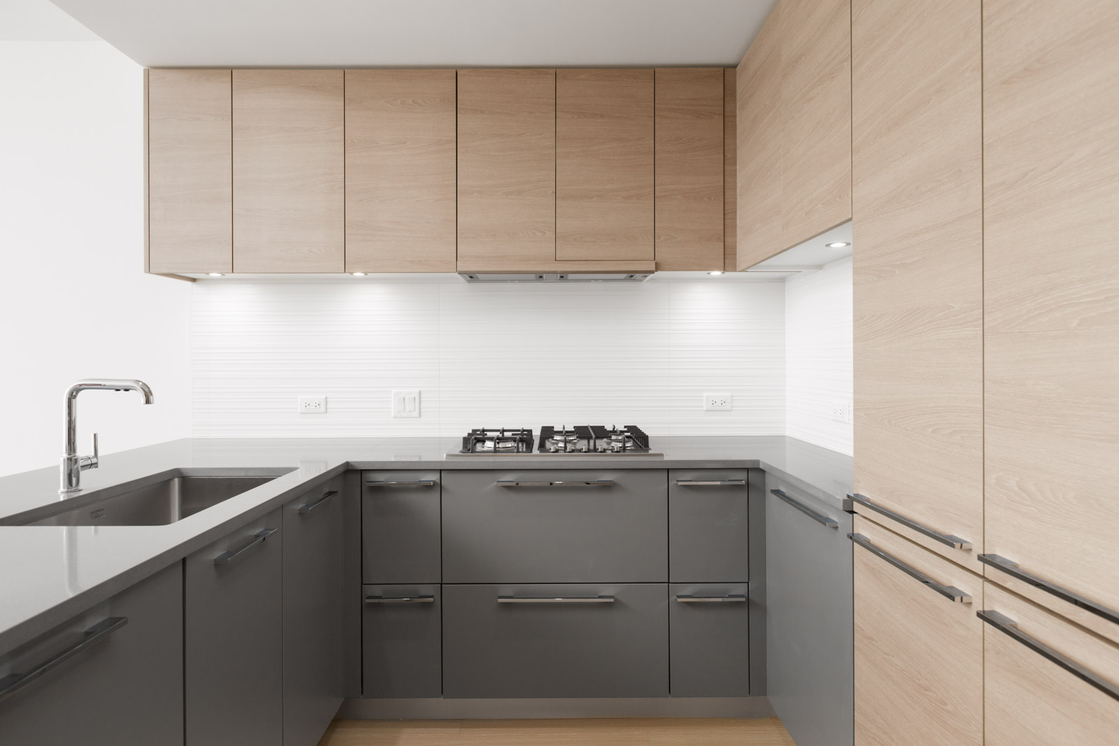 kitchen wall with stovetop in empty brand new condo managed by birds nest properties at kings crossing in burnaby