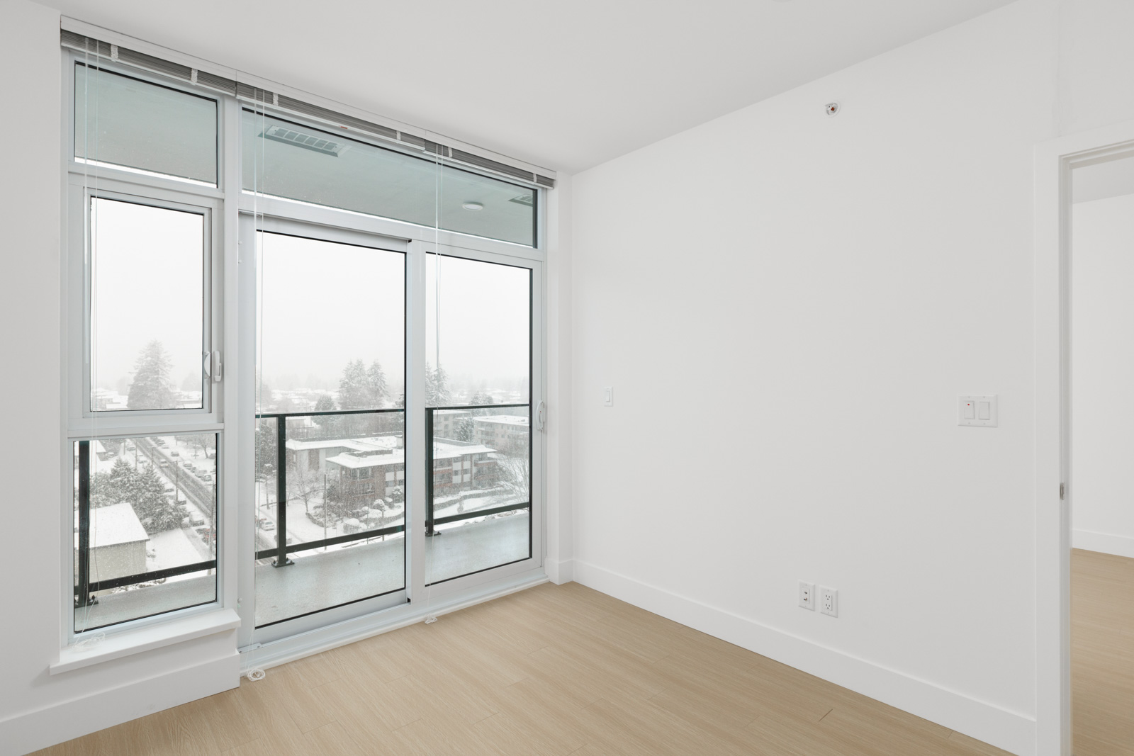 looking out floor to ceiling windows on left and while wall on right in empty brand new condo managed by birds nest properties at kings crossing in burnaby