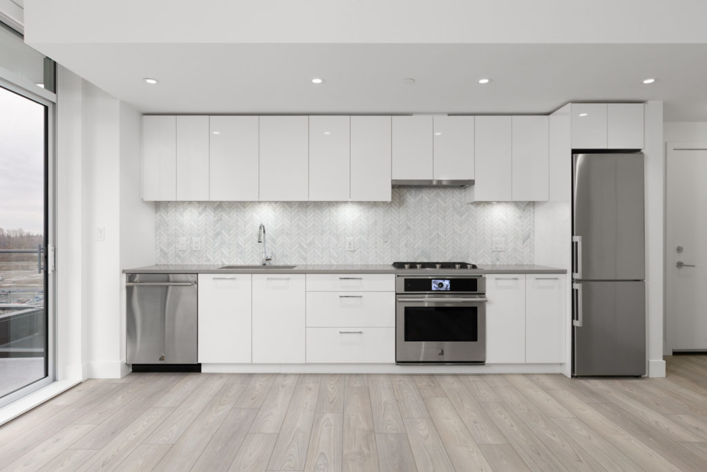 kitchen of empty condo managed by birds nest properties at avalon 2 at 8570 rivergrass drive in river district vancouver