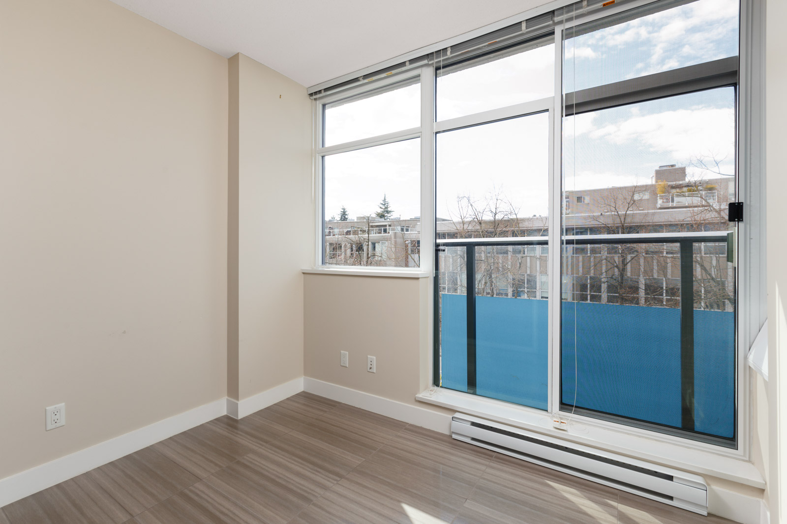 open living room with modern design and hardwood floors with bright lighting and balcony on the right in a rental condo in vancouver at kits360 on west 7th managed by birds nest properties