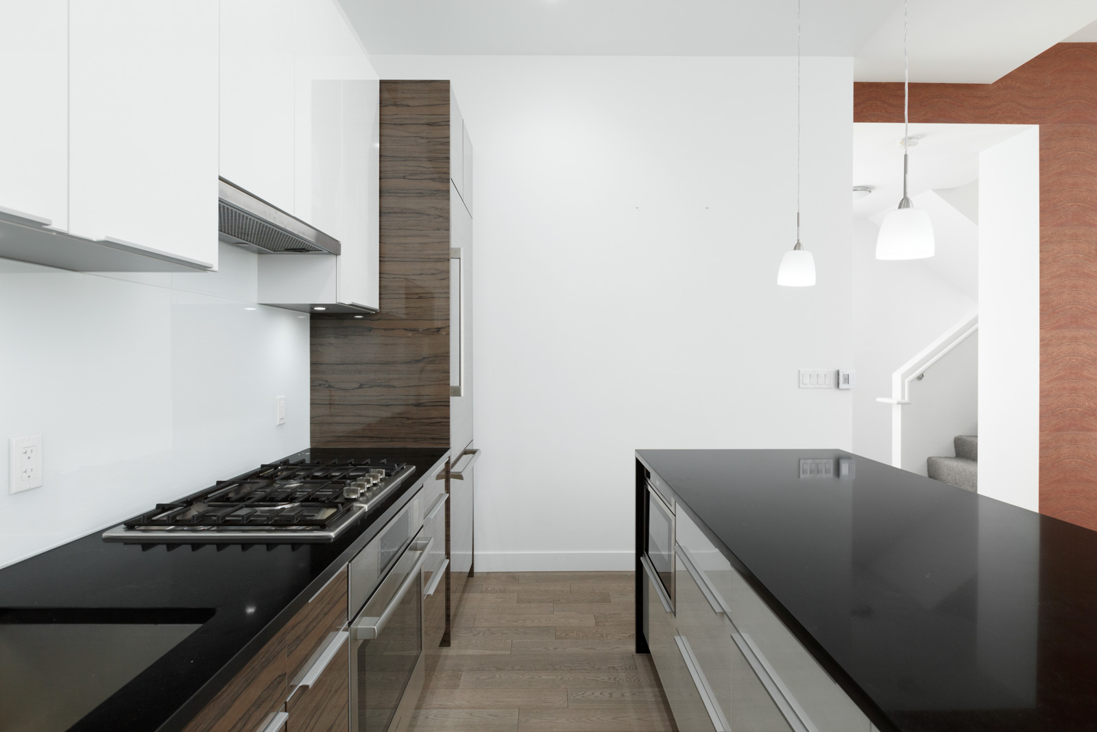 Spacious kitchen with white cabinetry and black quartz countertops with high end stainless steel appliances and natural gas cooktop stove in a rental townhouse in West Vancouver listed by Birds Nest Properties in Vancouver