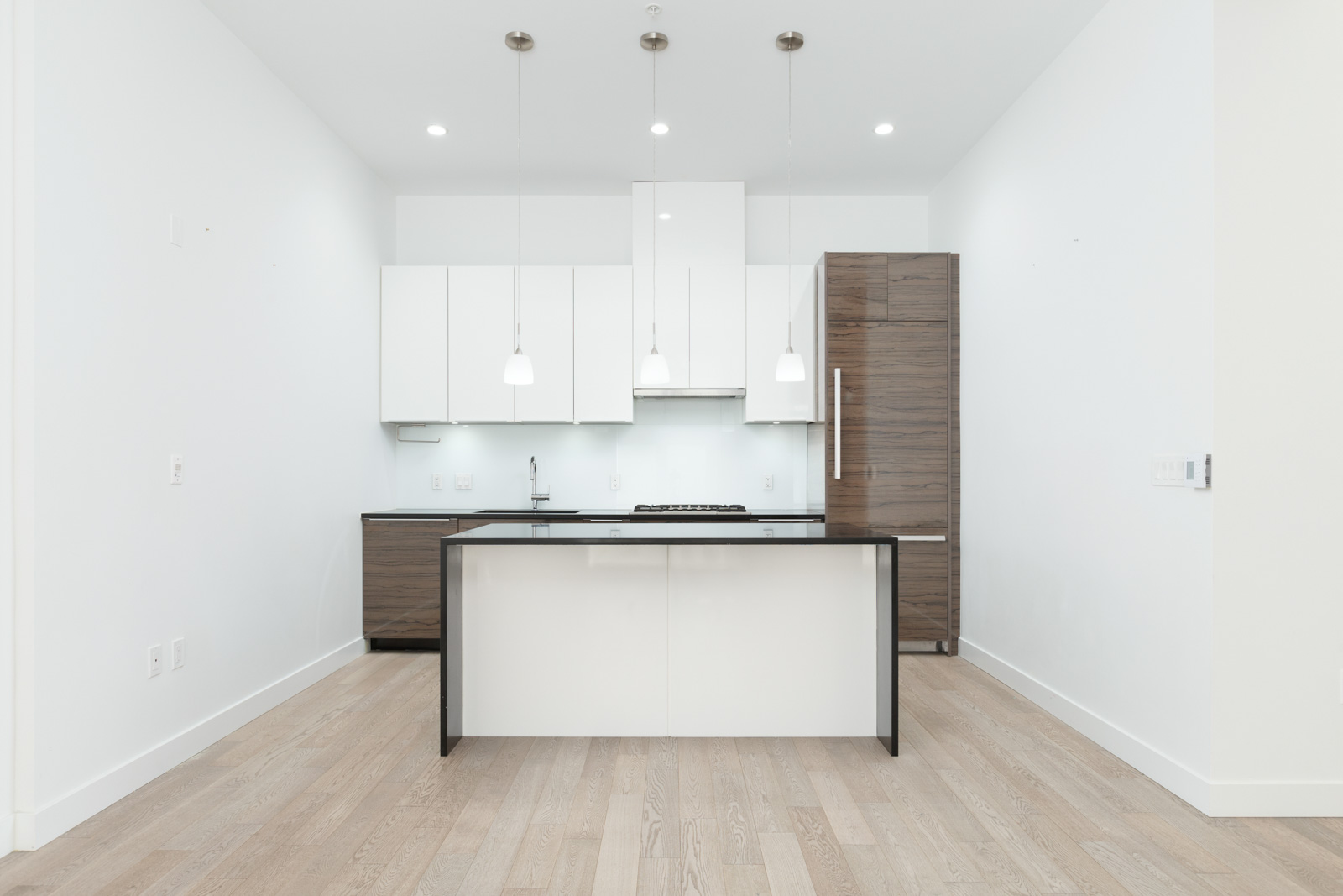 Spacious kitchen with white cabinetry and black quartz countertops with high end stainless steel appliances and natural gas cooktop and engineered hardwood flooring stove in a rental townhouse in West Vancouver listed by Birds Nest Properties in Vancouver