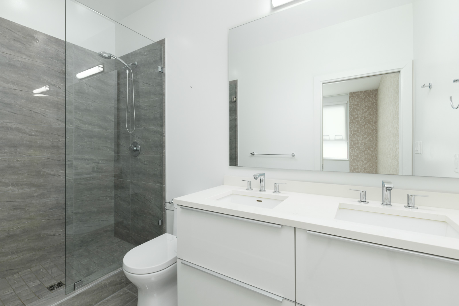Bathroom with double-sinks and modern bathroom fixtures and a large wall mirror in a rental townhouse in West Vancouver listed by Birds Nest Properties in Vancouver