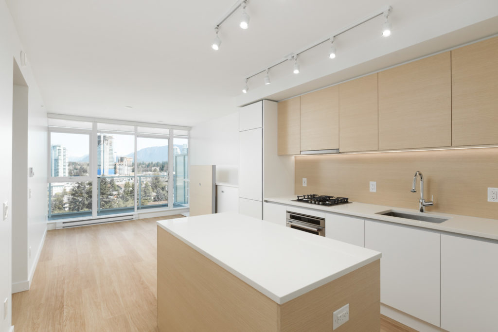 Bright spacious open kitchen with white quartz countertops and a kitchen island with outlets and new stainless steel appliances with natural lighting from floor-to-ceiling windows in a new condo in Coquitlam managed by Birds Nest Properties in Vancouver