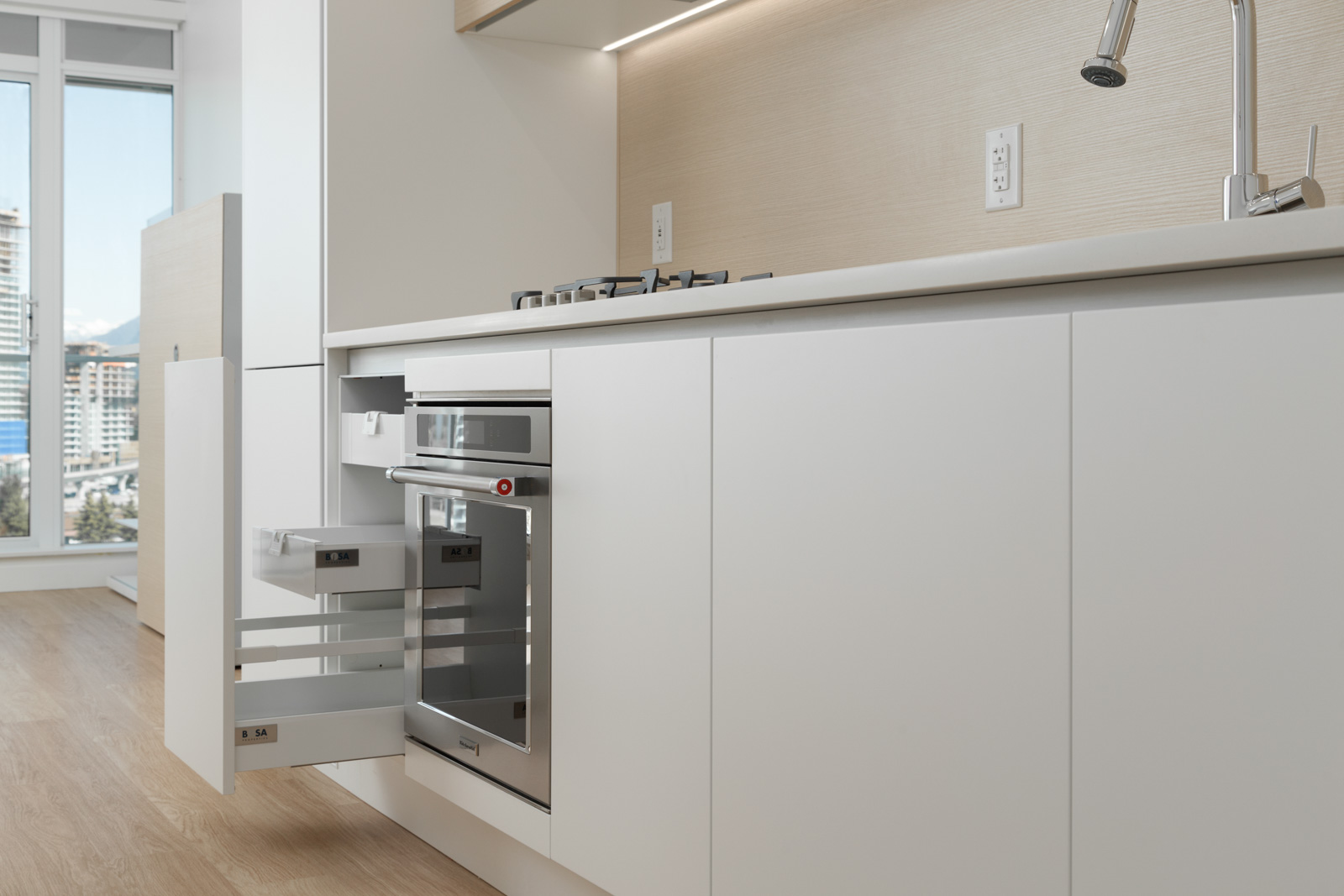 Bright spacious open kitchen with white quartz countertops and roll-out pantry storage and stainless steel oven and stove with storage cabinets brightly lit in a new condo in Coquitlam managed by Birds Nest Properties in Vancouver