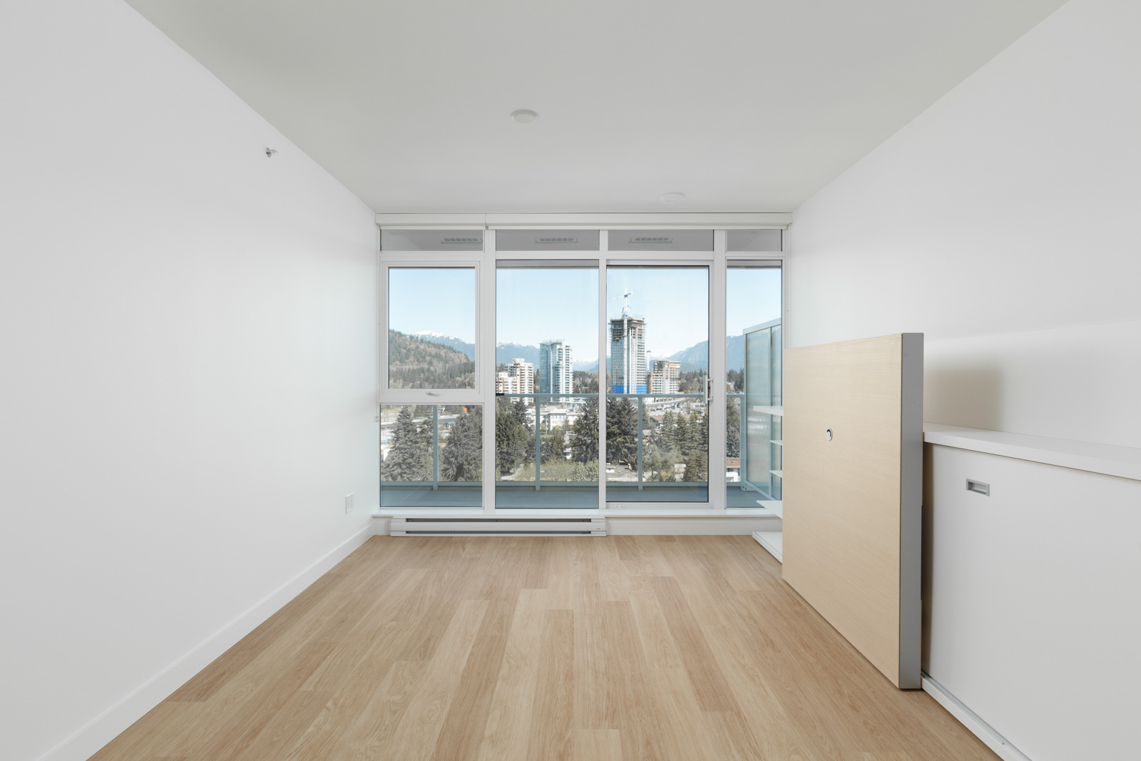 Bright spacious open living room with engineered hardwood flooring with natural lighting from floor-to-ceiling windows in a new condo in Coquitlam managed by Birds Nest Properties in Vancouver
