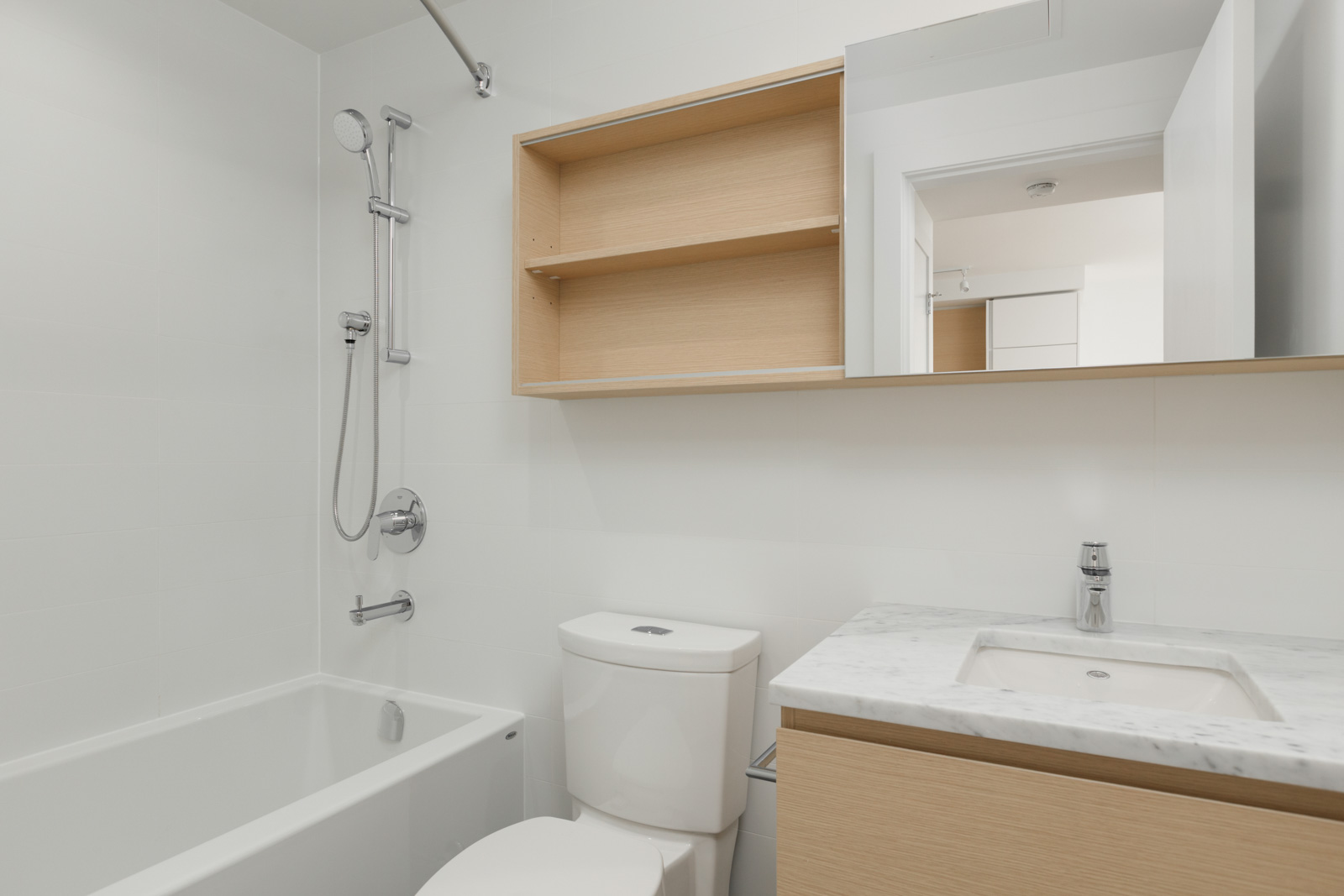 Bathroom with modern fixtures, porcelain toilet and quartz counter tops with wall shelving units and a mirror in a new condo in Coquitlam managed by Birds Nest Properties in Vancouver