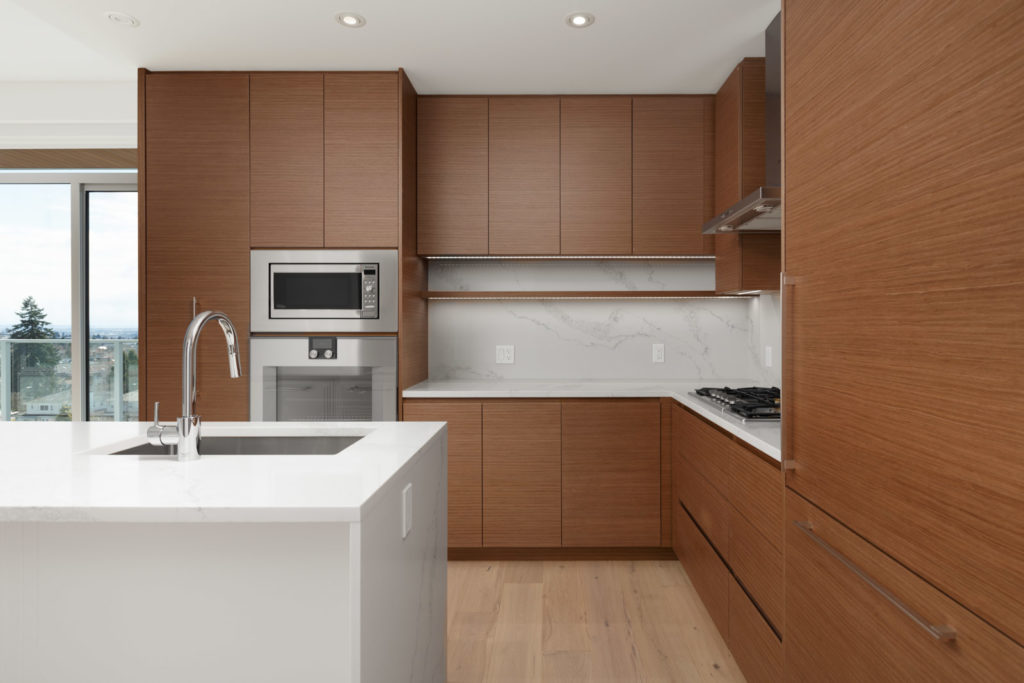 open kitchen with modern design and marble kitchen island and stainless steel sink dishwasher and refrigerator in a rental condo in vancouver at the parker on elizabeth street managed by birds nest properties