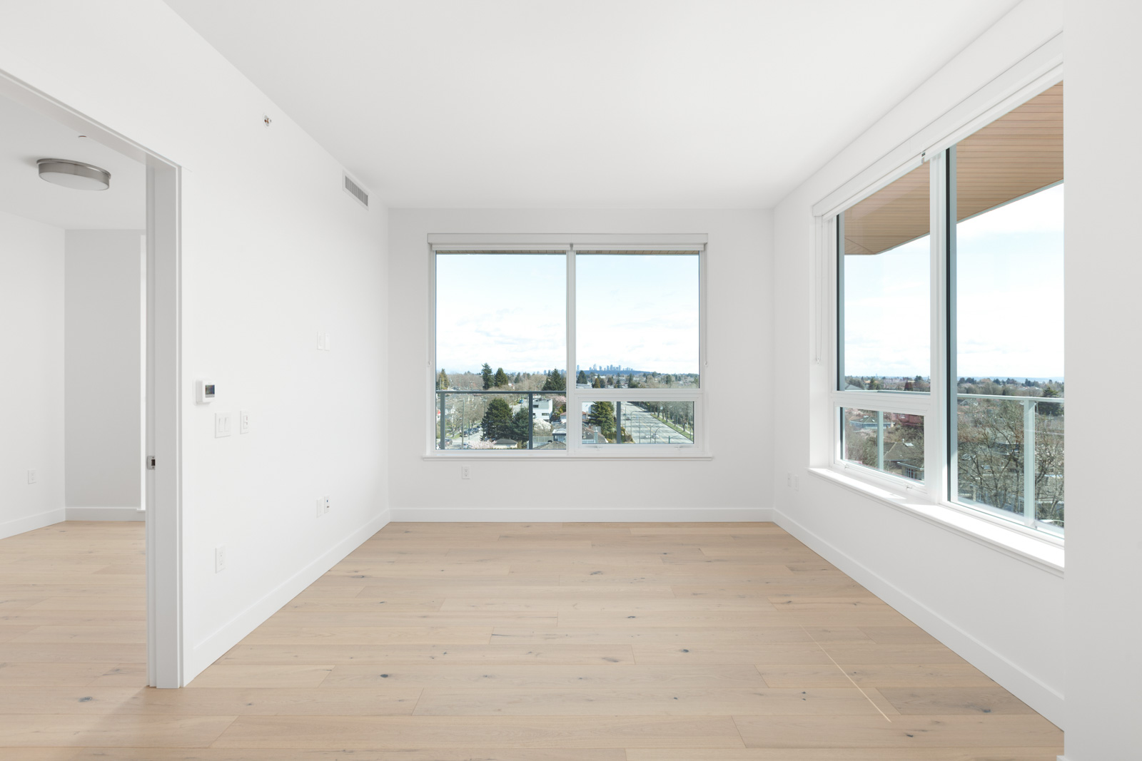 spacious living area with large windows and natural sunlight and light wooden flooring in a rental condo in vancouver at the parker on elizabeth street managed by birds nest properties