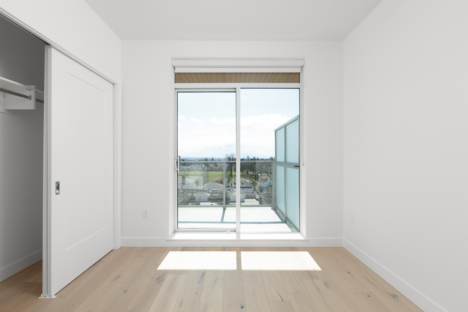 spacious bedroom with private balcony and large closet and natural sunlight and light wooden flooring in a rental condo in vancouver at the parker on elizabeth street managed by birds nest properties