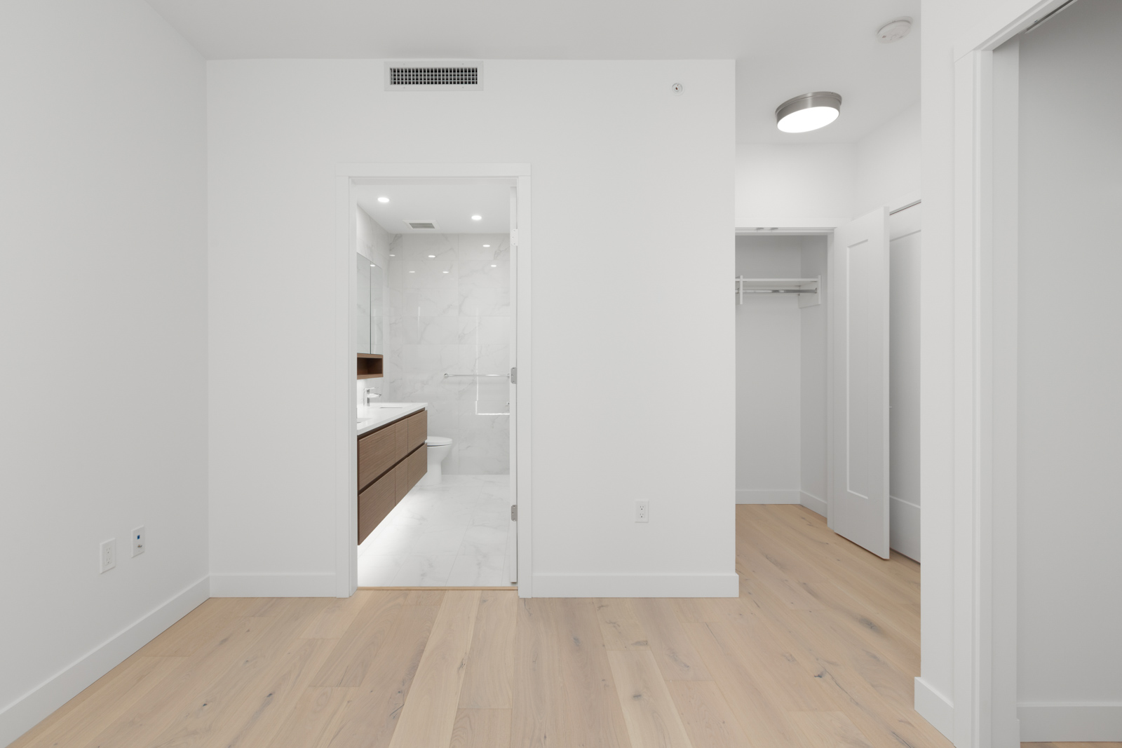 spacious bedroom with entrance to bathroom and natural sunlight and light wooden flooring in a rental condo in vancouver at the parker on elizabeth street managed by birds nest properties