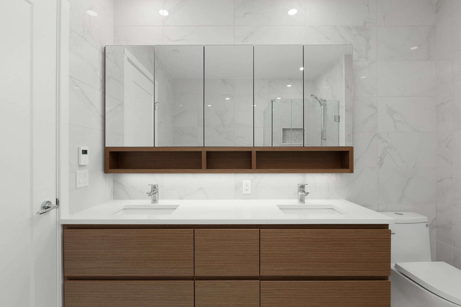 modern bathroom with two sinks and large mirror cabinet storage with additional under the sink storage and light wooden flooring in a rental condo in vancouver at the parker on elizabeth street managed by birds nest properties