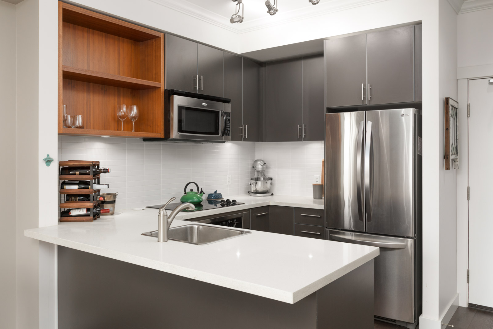 Modern kitchen with stainless steel fridge and microwave and granite countertops with storage cabinets in a rental condo in East Vancouver offered by Birds Nest Properties