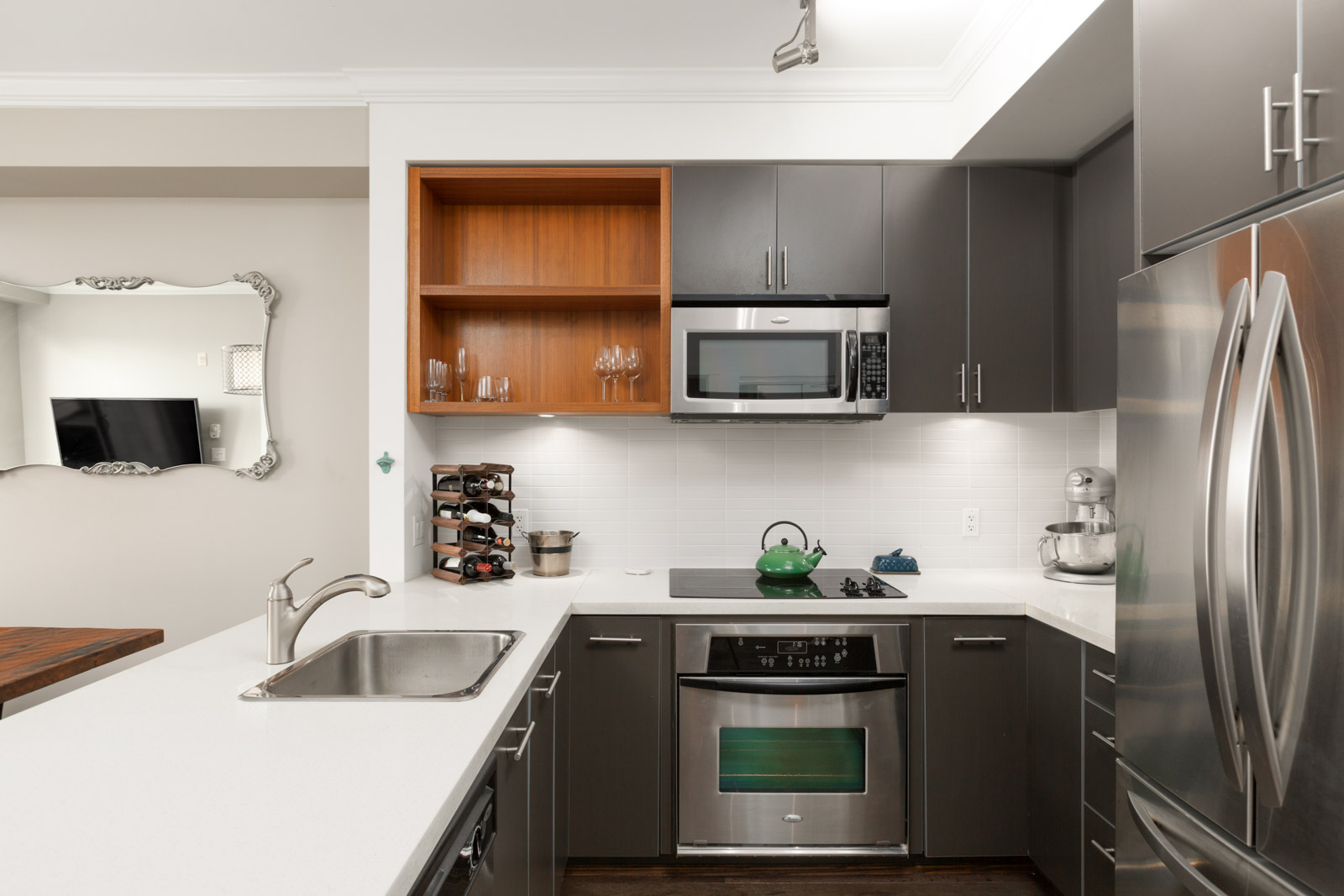 Modern kitchen with stainless steel fridge, sink, oven, and microwave with granite countertops and storage cabinets in a rental condo in East Vancouver offered by Birds Nest Properties
