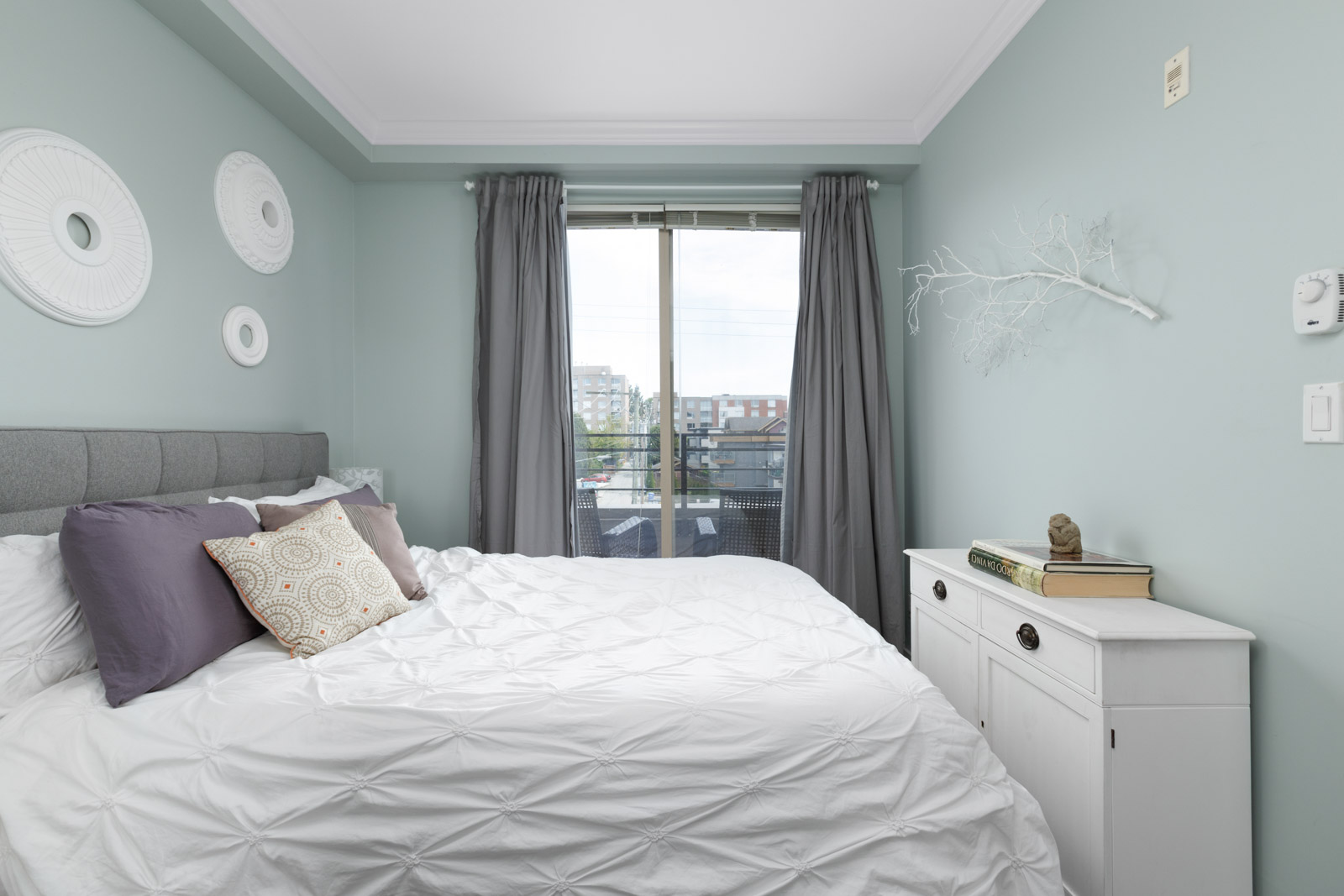 Spacious bedroom with floor-to-ceiling windows providing natural sunlight in a rental condo in East Vancouver offered by Birds Nest Properties