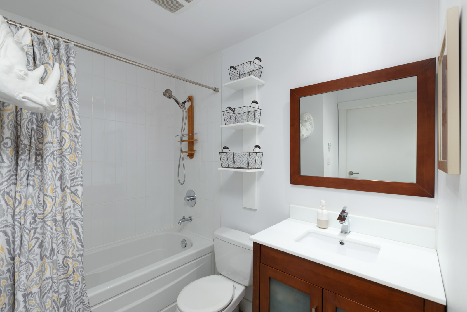 Cozy washroom with modern bathroom fixtures and sink storage in a rental condo in East Vancouver offered by Birds Nest Properties