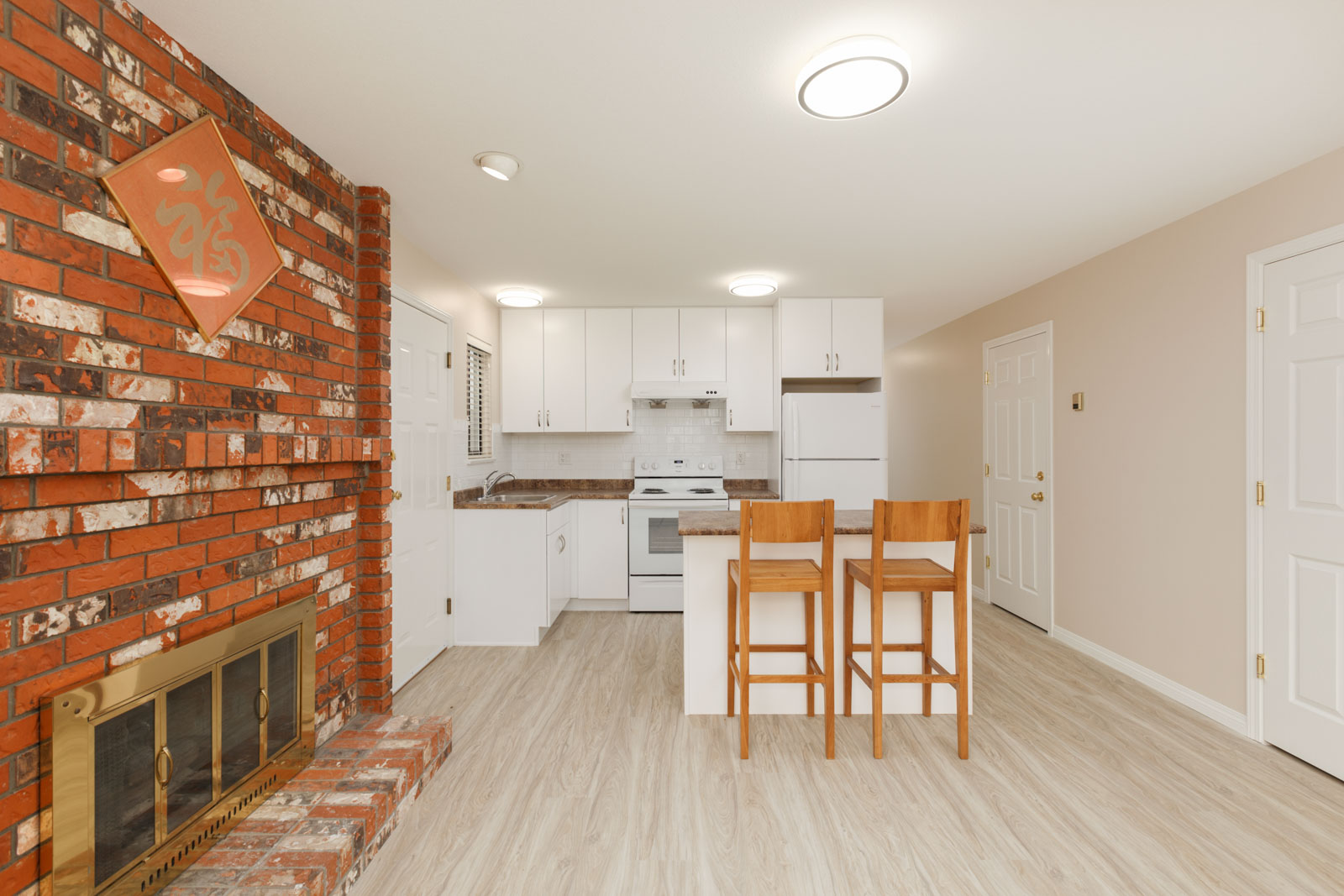 Cozy living area with an authentic brick fireplace to the right of the suite and a kitchen with full range of appliances and a kitchen island to the left, inside a unit with laminate hardwood flooring in a rental home in East Vancouver provided by Birds Nest Properties