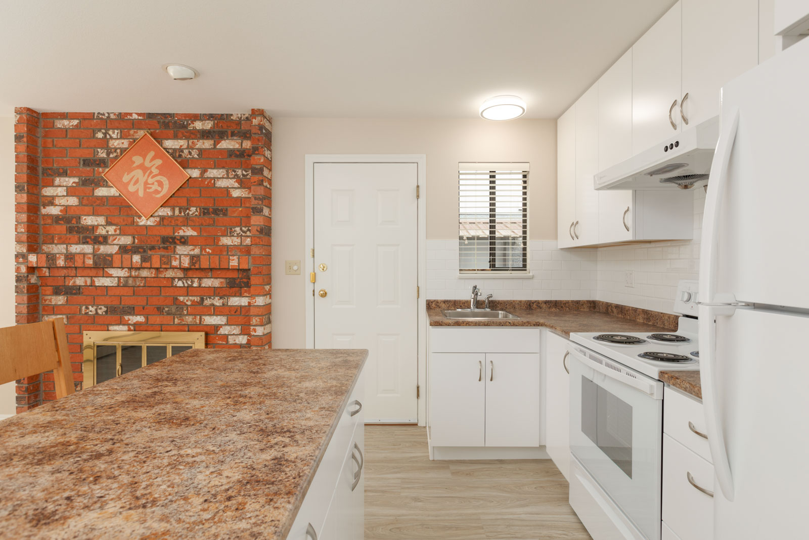 Cozy living area with an authentic brick fireplace in the suite and a kitchen with full range of appliances and storage space with a kitchen island, inside a unit with laminate hardwood flooring in a rental home in East Vancouver provided by Birds Nest Properties