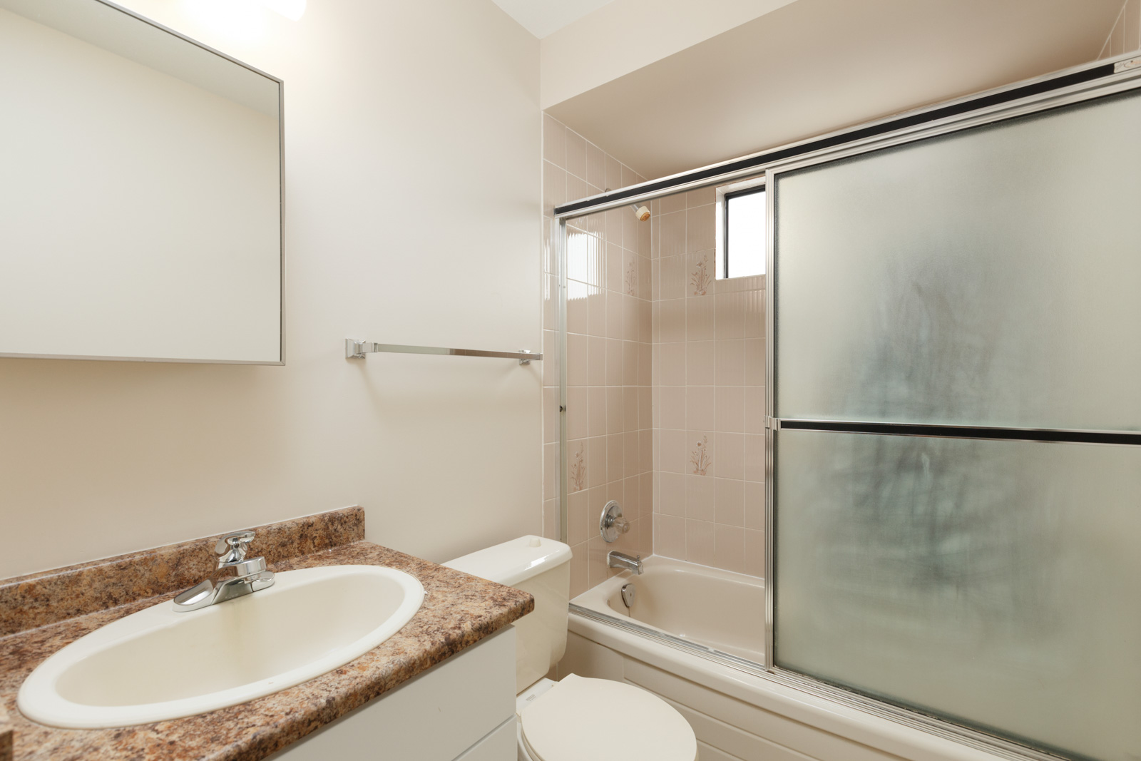 Bathroom with mirror over sink with granite countertops and shower with sliding glass door and window providing fresh air and natural light in a rental home in East Vancouver provided by Birds Nest Properties