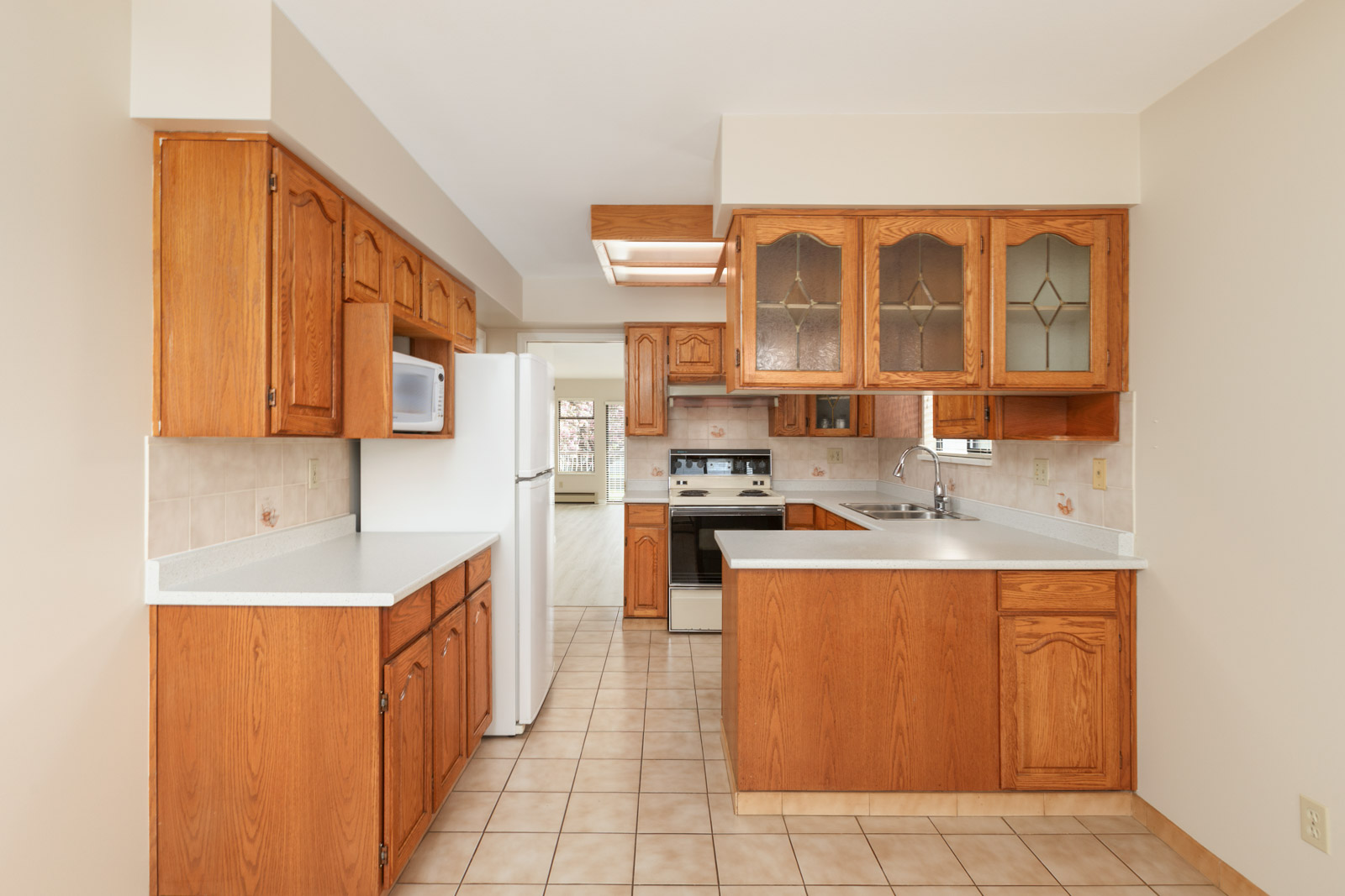 Open kitchen with full range of appliances, with a refrigerator, stove, oven, sink, and cabinetry providing storage space with tiled flooring in a rental home in East Vancouver provided by Birds Nest Properties
