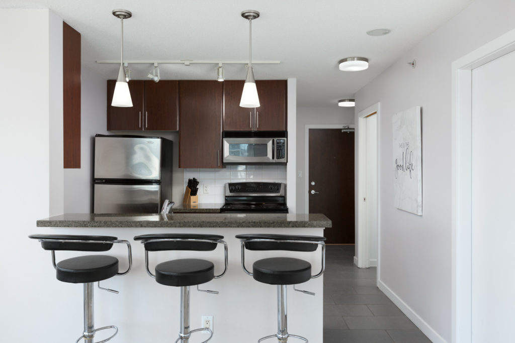 spacious kitchen with island and barstool seating with modern light fixtures above and high-end appliances in a rental condo in vancouver offered by Birds Nest Properties