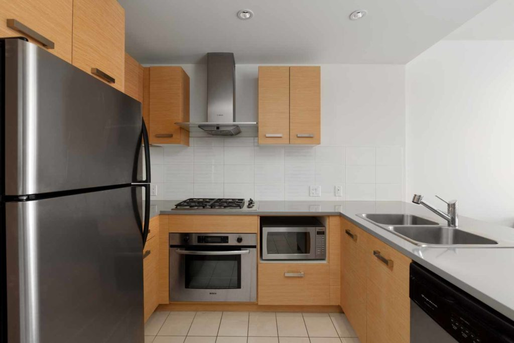 Open kitchen with high-end stainless steel appliances including oven, stove, refrigerator, and sink, with plenty of counter and storage space in a rental condo in Richmond offered by Birds Nest Properties