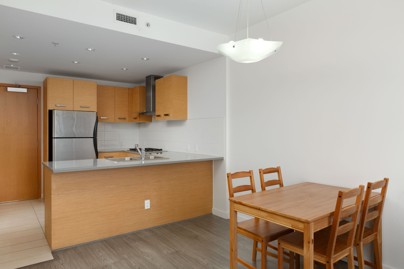 Open kitchen with outlets and dining area and laminate hardwood flooring in a rental condo in Richmond offered by Birds Nest Properties