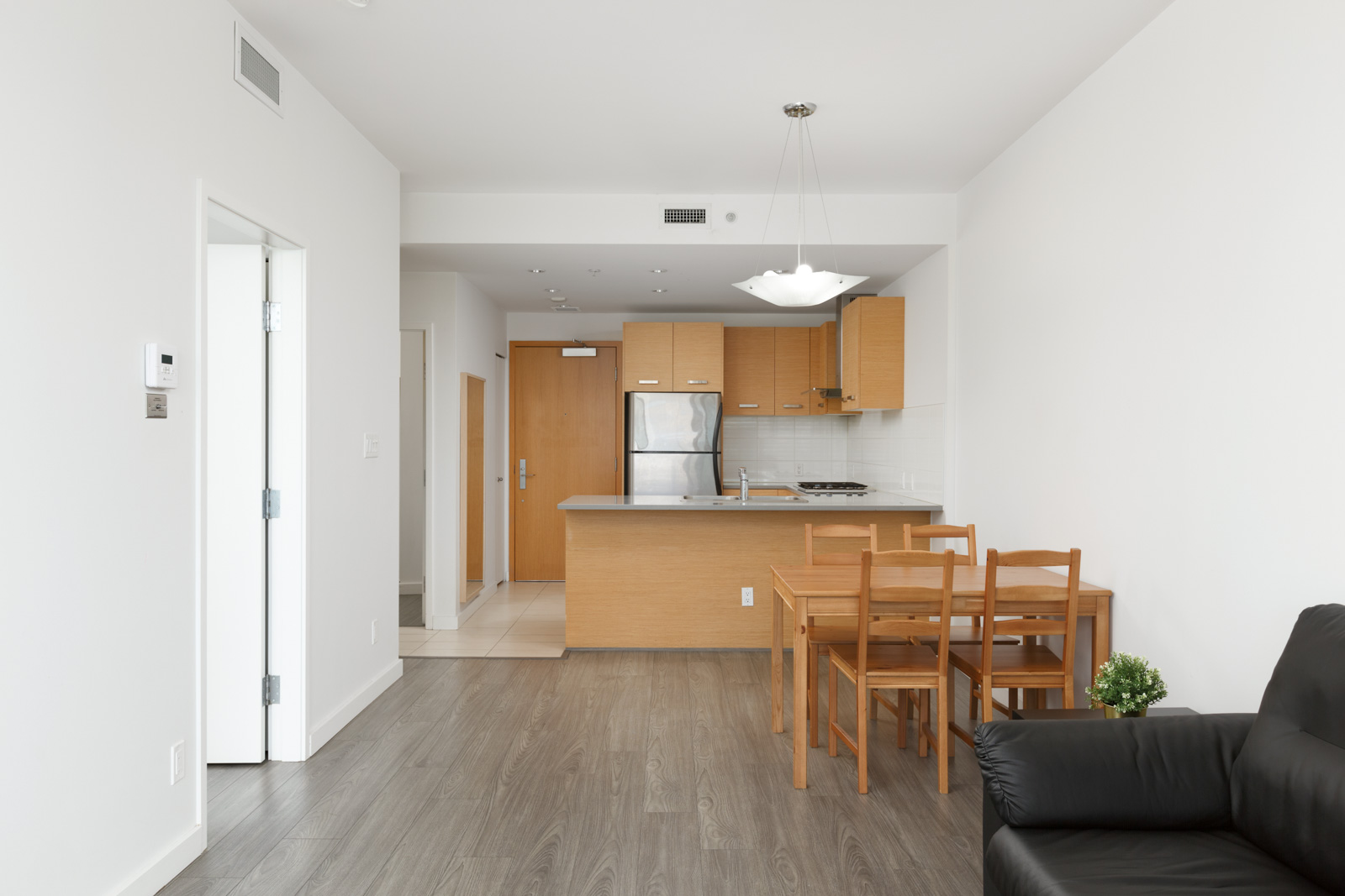 Spacious kitchen leading into open living room area with natural lighting and laminate hardwood flooring in a rental condo in Richmond offered by Birds Nest Properties