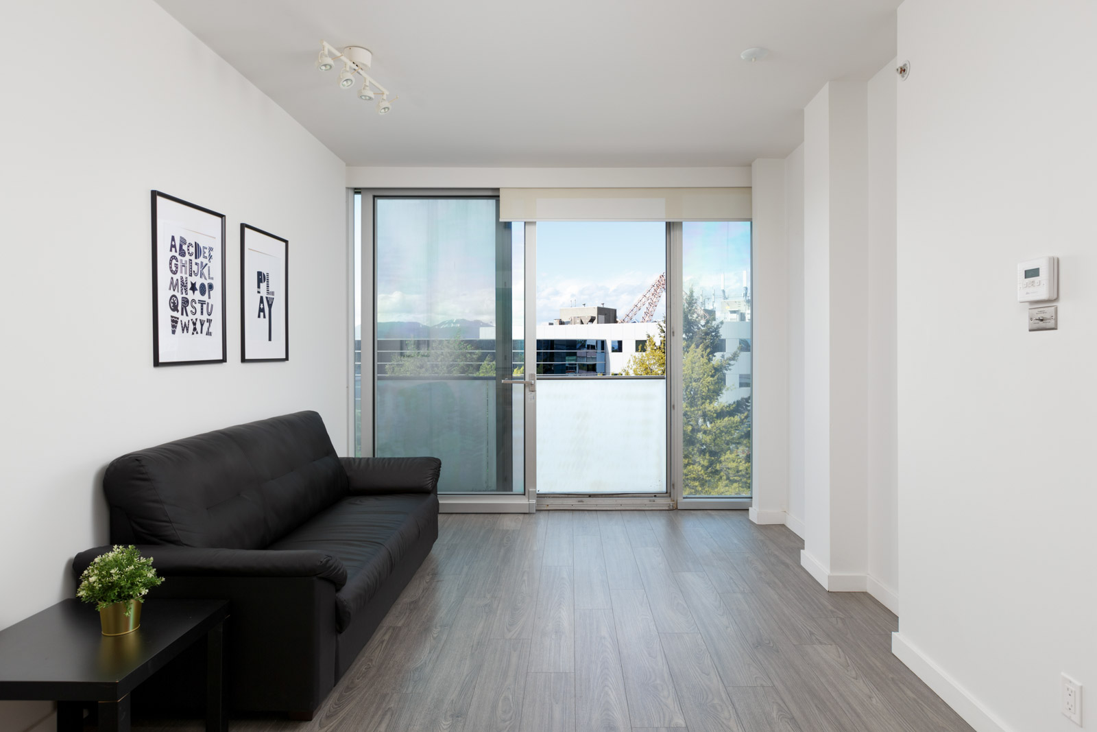 Floor-to-ceiling windows providing natural sunlight into the living room in a rental condo in Richmond offered by Birds Nest Properties