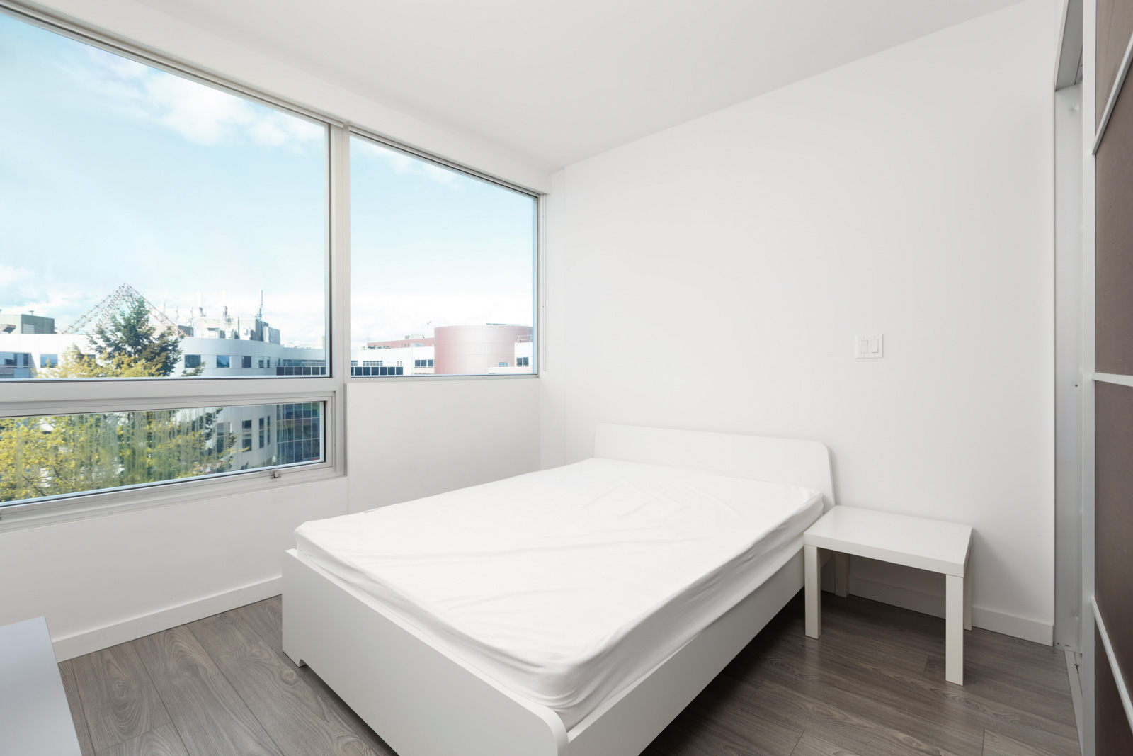 Bedroom with natural sunlight provided by large windows in a rental condo in Richmond offered by Birds Nest Properties