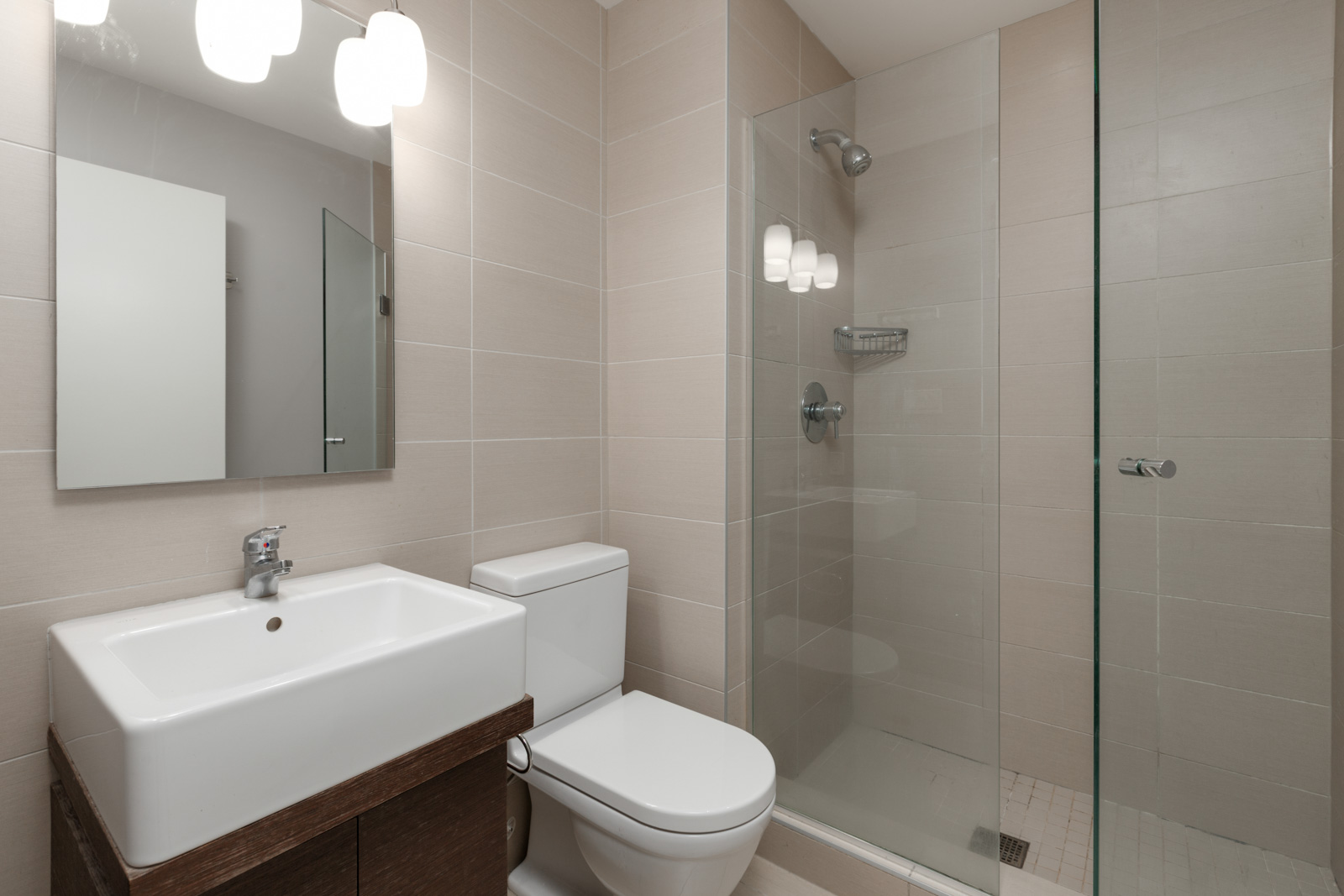 Cozy bathroom with lighting fixtures over mirror and sink in bathroom in a rental condo in Richmond offered by Birds Nest Properties