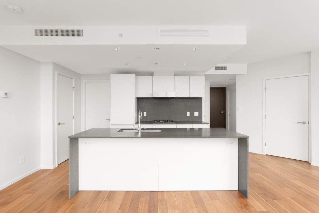 Spacious kitchen with large kitchen island with quartz countertops and high-end stainless steel appliances and engineered hardwood flooring in a rental condo in Vancouver offered by Birds Nest Properties