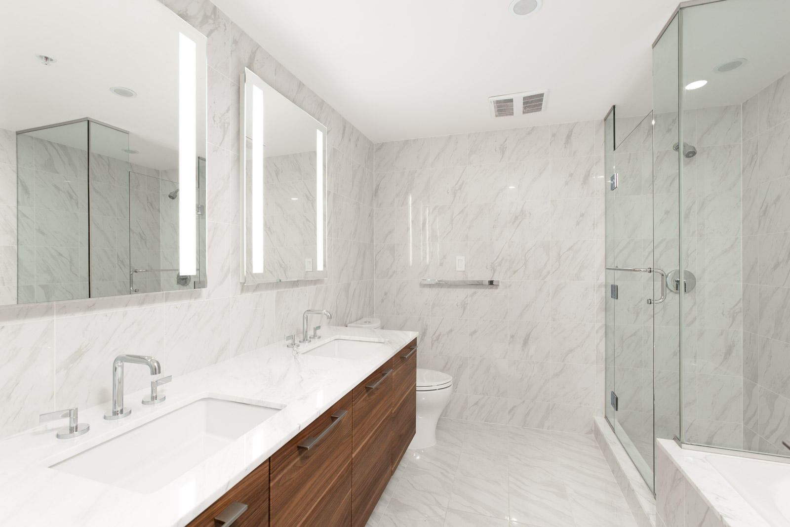 Spacious bathroom with modern bathroom fixtures; large mirrors with adequate lighting and marble countertops with sink storage underneath, and a shower finished with a sleek glass door in a rental condo in Vancouver offered by Birds Nest Properties