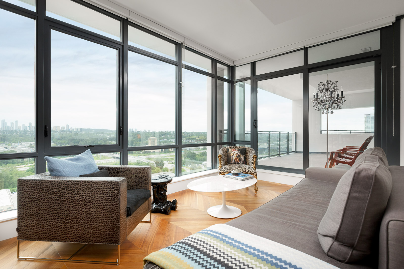 Large floor-to-ceiling windows providing natural sunlight with entertainment space and access to the balcony in a rental condo in Burnaby offered by Birds Nest Properties.