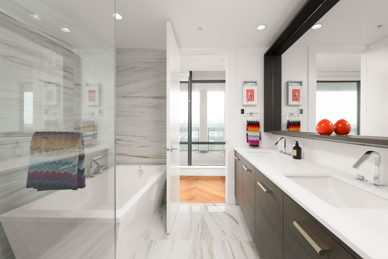 Modern bathroom with double sinks and under-the-sink storage, with a large mirror overhead. Glass doors enclose the bathtub, and the room is lit with ceiling lights in a rental condo in Burnaby offered by Birds Nest Properties.
