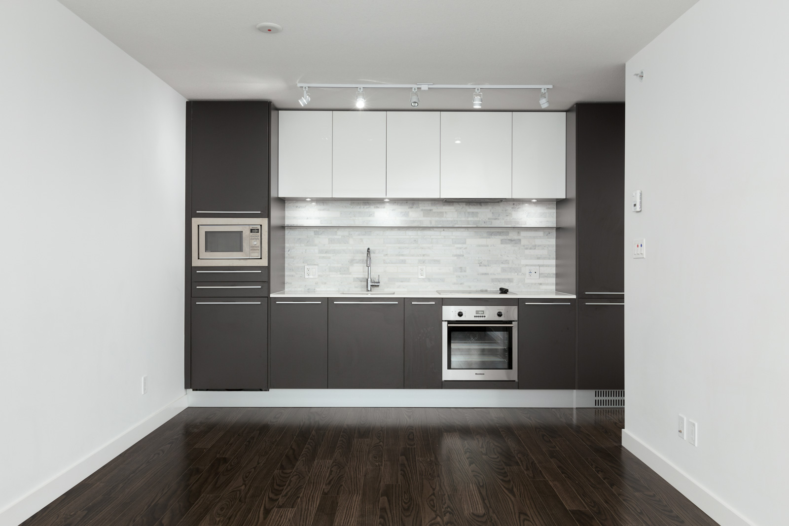 Modern kitchen with stainless steel oven, microwave and sink with plenty of shelf storage and overhead lighting. The unit has laminate hardwood flooring, and plenty of natural light in a rental condo in Vancouver offered by Birds Nest Properties.