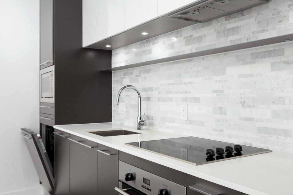 Sleek kitchen with a tiled backsplash and high-end appliances such as a dishwasher, microwave, stovetop on quartz countertops in a rental condo in Vancouver offered by Birds Nest Properties.