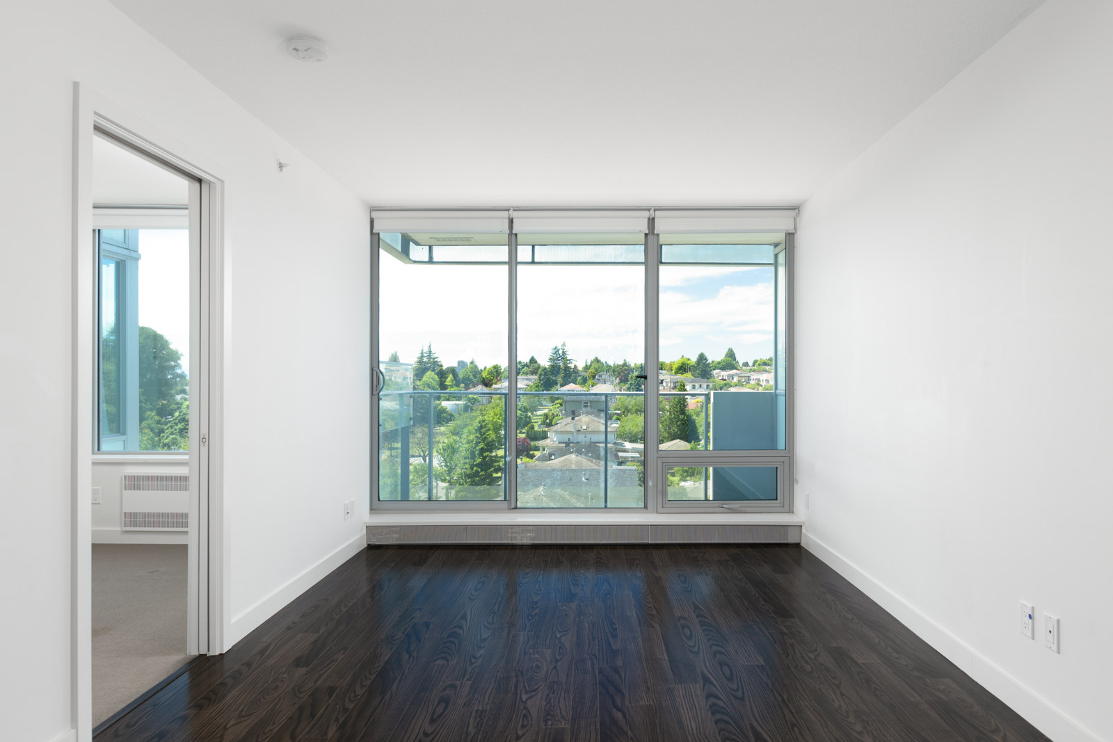 Spacious living area with natural lighting offered by close access to the balcony with laminate hardwood flooring in a rental condo in Vancouver offered by Birds Nest Properties.