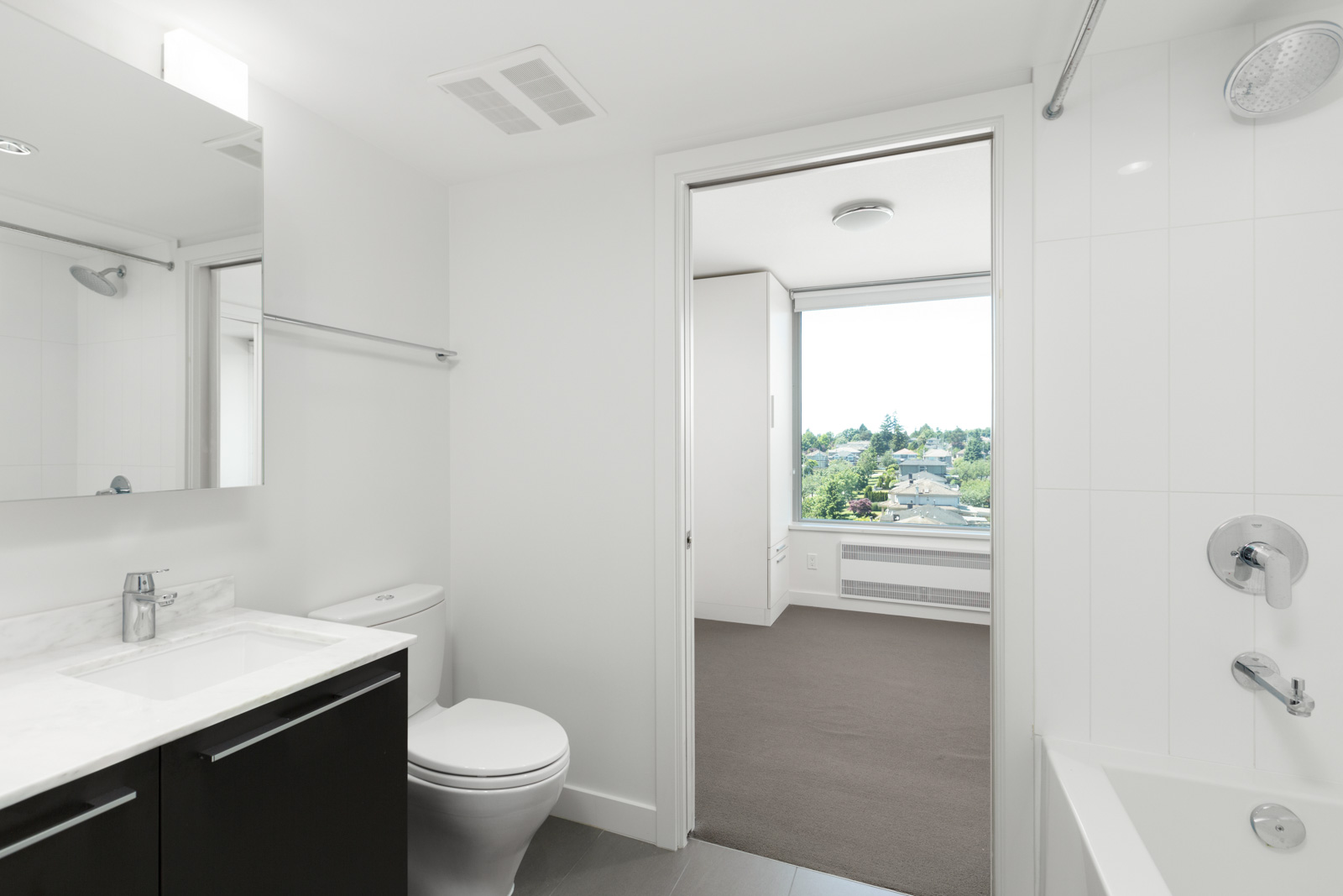 Elegant bathroom with under-the-sink storage and mirror over the sink with a bathtub, showerhead, and ventilation in a rental condo in Vancouver offered by Birds Nest Properties.
