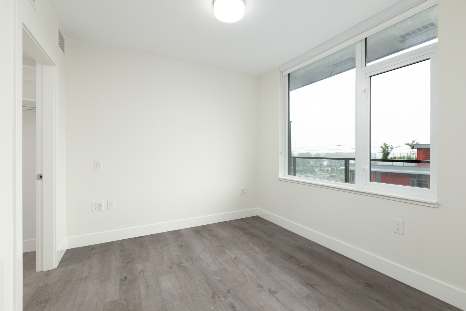 bedroom with white walls and hardwood floors in rental condo in the Downtown neighbourhood of Vancouver