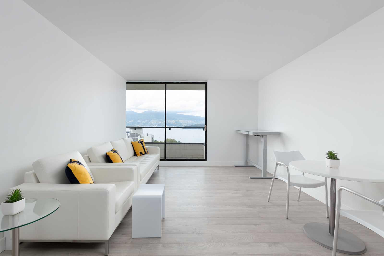 living room of rental property with sofa on left and window looking out over kitsilano beach of vancouver