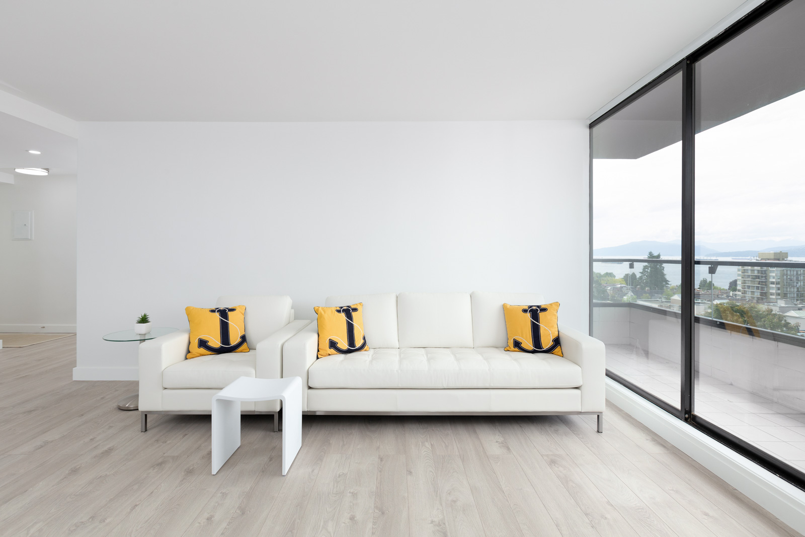 living room of rental property with sofa against wall and yellow pillows with window on the right in kitsilano vancouver