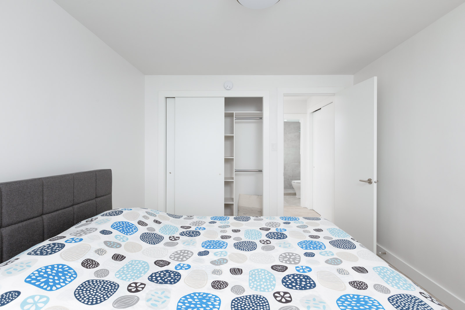 bed with polka dot sheets with opened door closet in background in rental condo in kitsilano