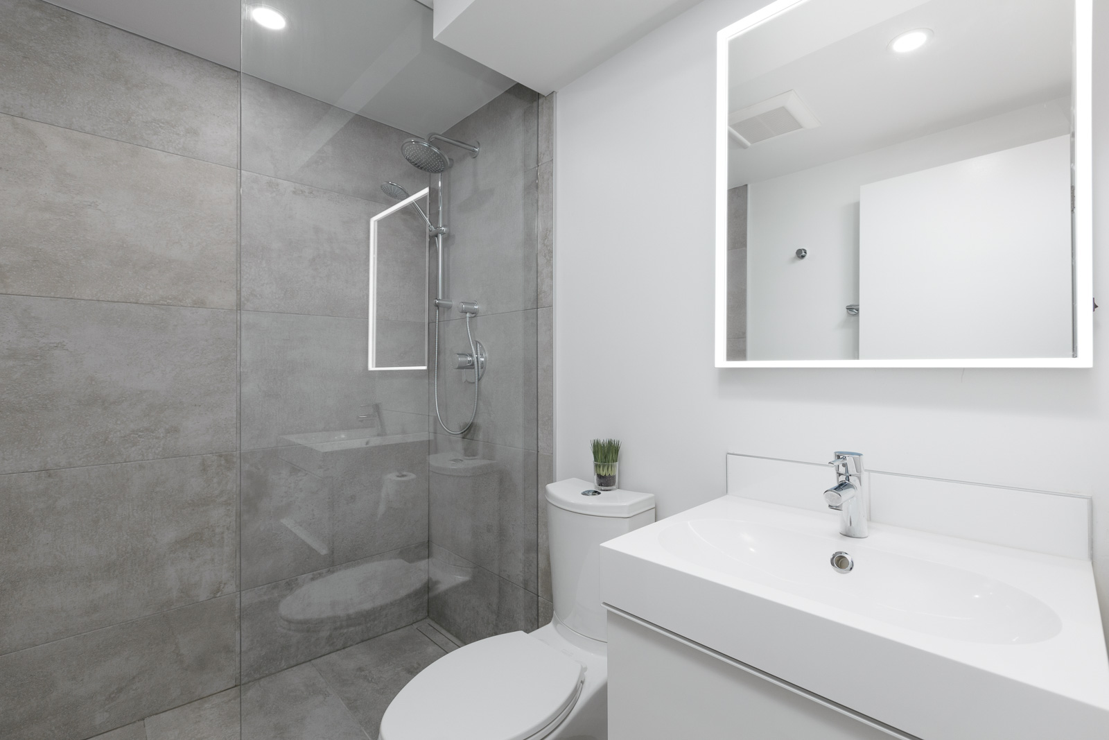 bathroom of rental condo with granite tiles in shower on left and vanity on right with vancouver property management