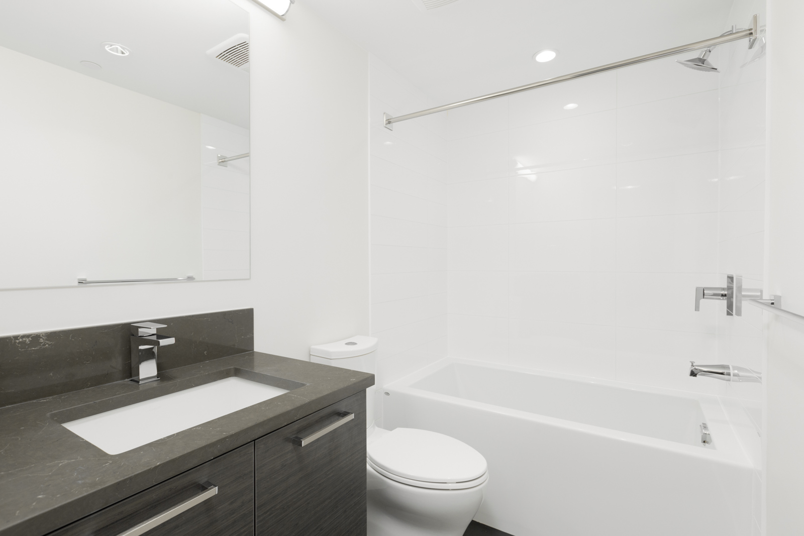bathroom with white tile, tub, and huge mirror