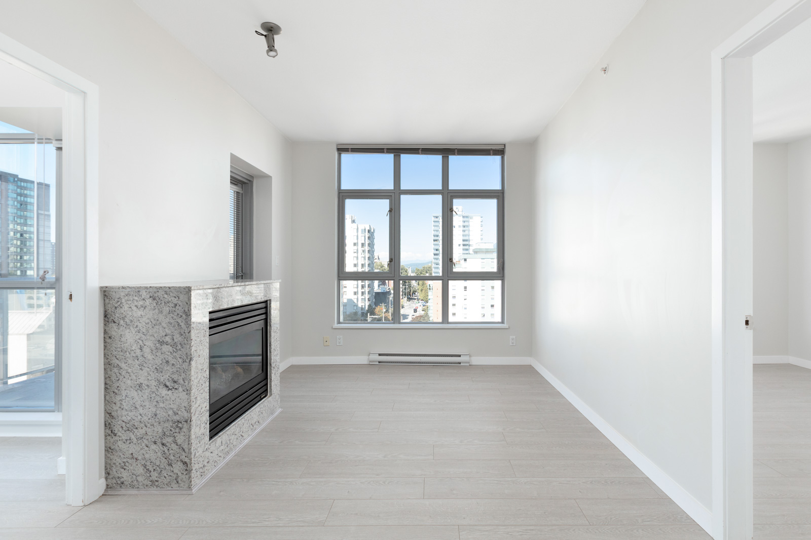 living room with fireplace on left and windows in background in rental property at the sterling building in the west end of downtown vancouver