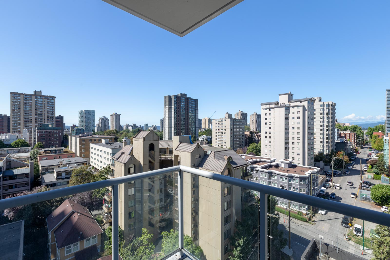 view of buildings and blue sky from balcony of rental property at sterling condo building in west end neighbourhood of downtown vancouver