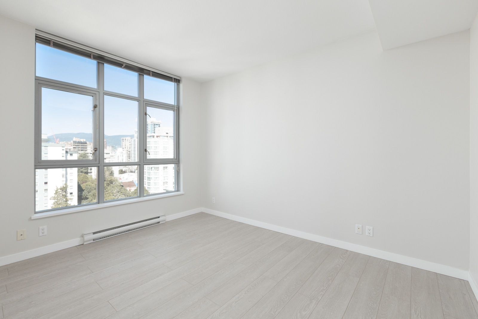bedroom with white walls and bright windows on left in rental property at the sterling building in the west end of downtown vancouver