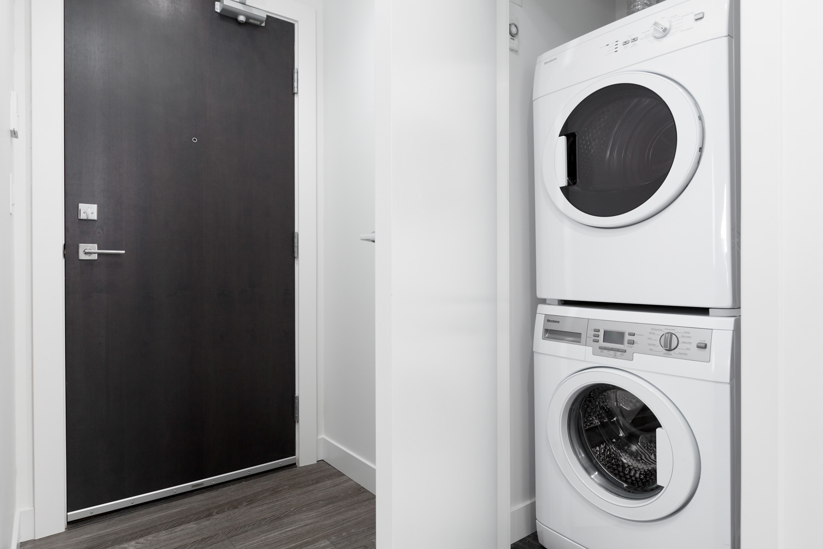 dark entry door on left and washer dryer on right of rental condo in the Yaletown neighbourhood of Vancouver